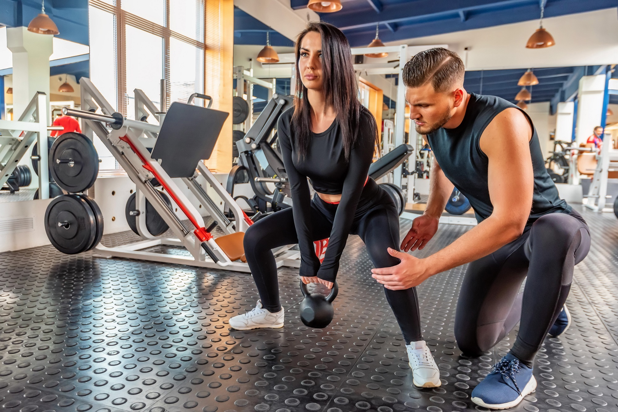 Personal trainer coaching female bodybuilder making plie squat with dumbbell
